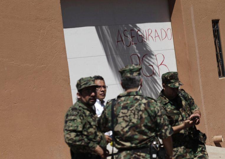 Militairen posten bij een woning in Culiacán die eigendom is van de opgepakte drugsbaas Guzmán. Beeld reuters