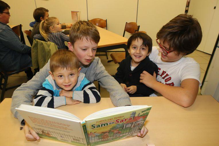 Kinderen lezen voor aan kleuters.