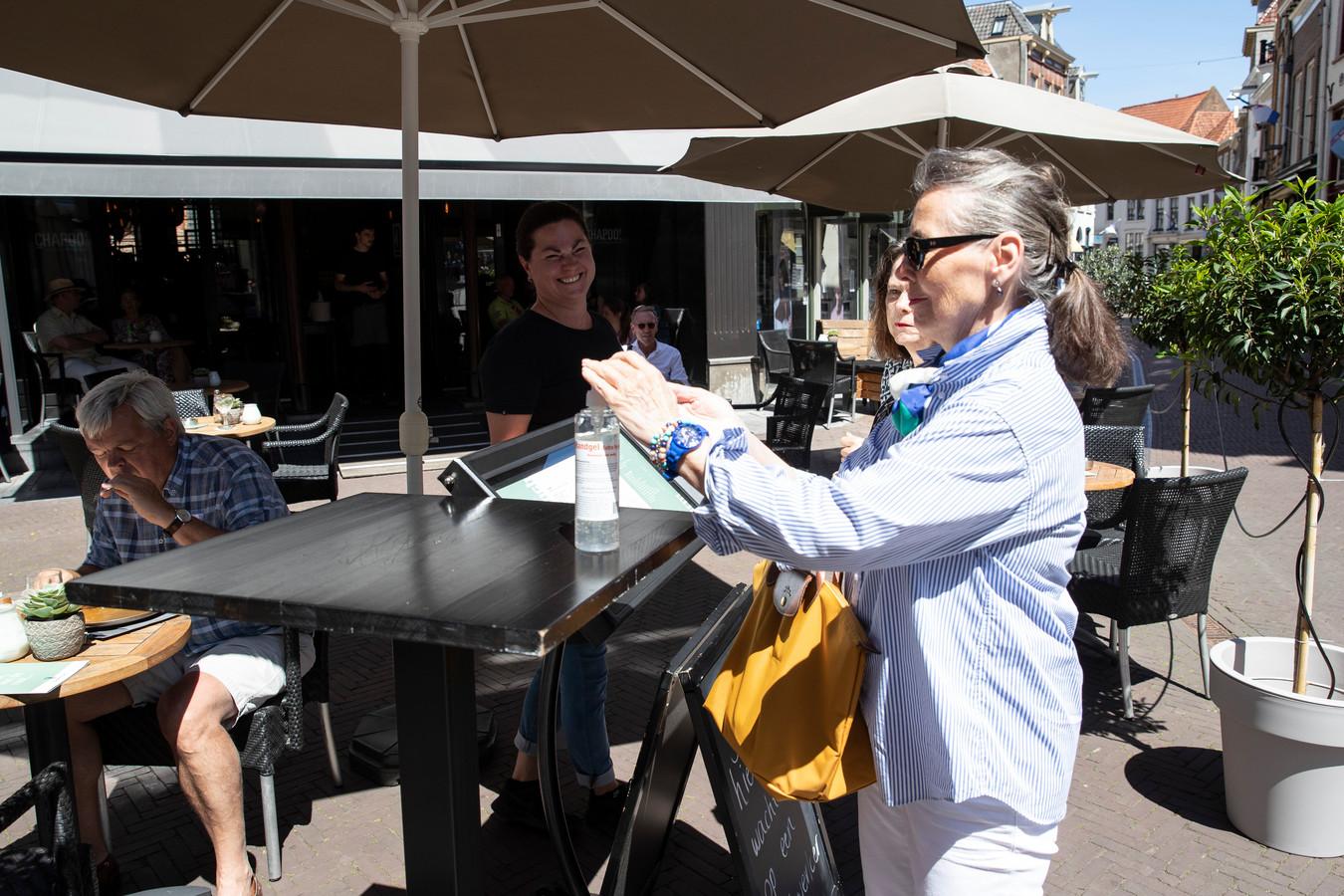 De horeca in Zutphen mag weer open. Bij Chapoo! staat Silja Dozeman klaar om de gasten te verwelkomen. Iedereen moet wel eerst de handen ontsmetten voordat ze gebruik kunnen maken van het terras.