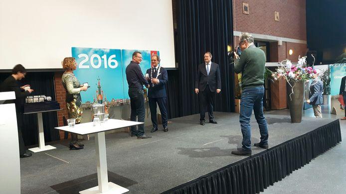 Burgemeester Rombouts deelt de medailles uit.