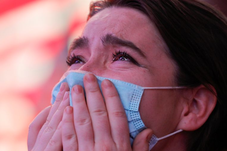 Krista Matheny (26) kijkt de overwinningsspeech van Joe Biden op Times Squar in New York City.  Beeld REUTERS