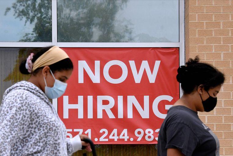 Personeel gezocht bij een winkel in Arlington, in de Amerikaanse deelstaat Virginia. De deltavariant van het coronavirus heeft z'n weerslag op de Amerikaanse arbeidsmarkt, blijkt uit nieuwe cijfers van het ministerie van arbeid. Beeld AFP