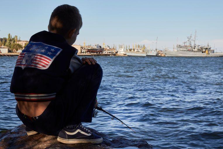 Een kind vist bij de Oekraïnese marinebasis in Otsjakiv, die wordt gerenoveerd door de Verenigde Staten. Beeld NAVY / Zwarte Zee in Oekraine. foto Pierre Crom