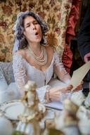 De verlaten bruid Miss Havisham draagt een gedicht voor in de etalage in de Golstraat.