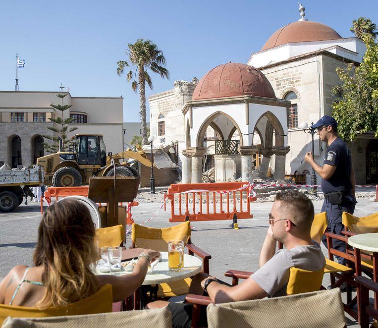 2017-07-22 15:17:19 KOS - Toersiten bekijken de schade die is ontstaan door de aardbeving op het Griekse eiland Kos. ANP JERRY LAMPEN Beeld ANP