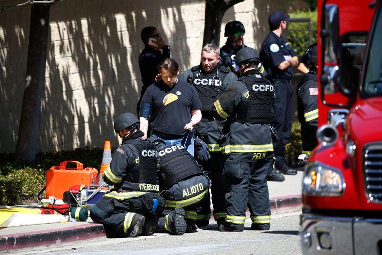 Medisch personeel met kogelvrije vesten aan behandelt ter plaatse een man.