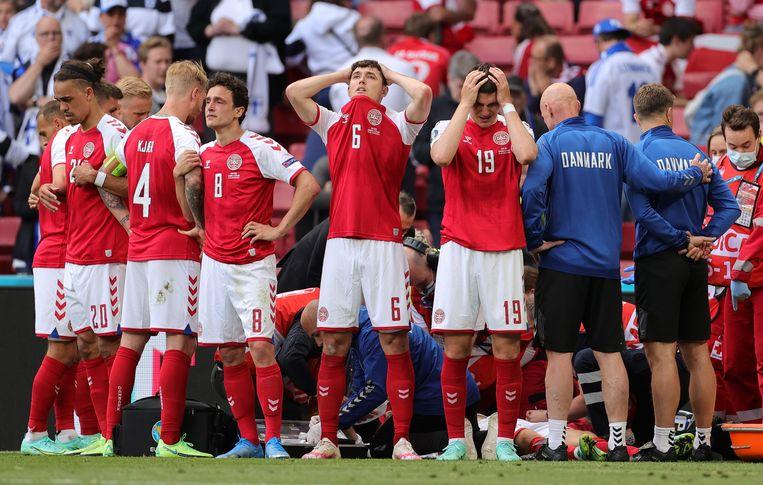 De spelers van Denemarken hebben zaterdag een cordon gevormd rond Christian Eriksen. Beeld EPA