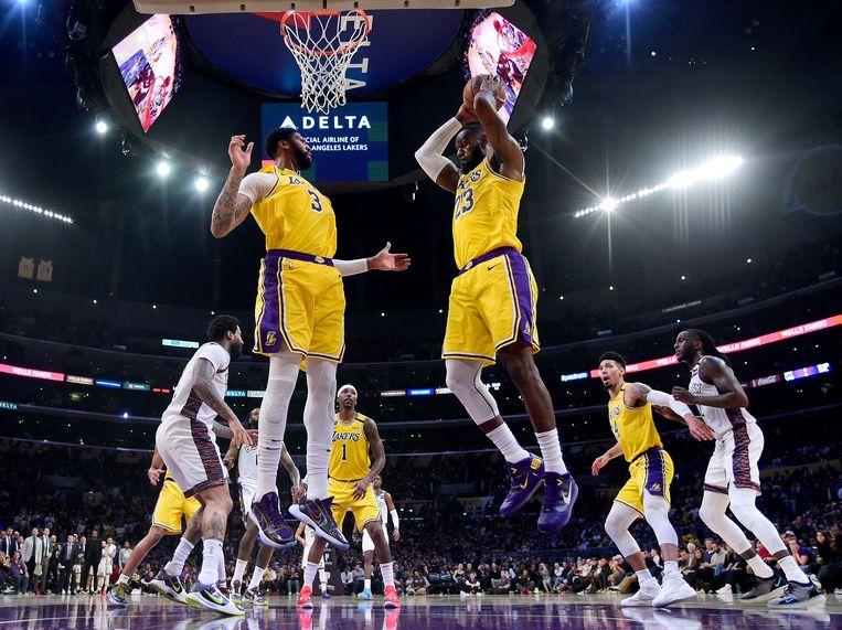 LeBron James plukt de bal uit de lucht, Anthony Davis springt mee in steun. De twee vormen nog steeds het sterkste duo in de NBA. Beeld AFP