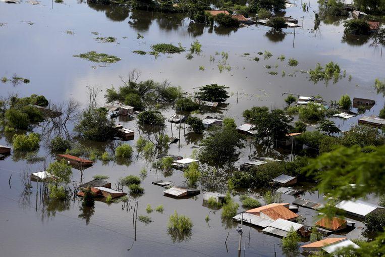 Huizen staan onder water in de Paraguayaanse hoofdstad Asuncion. In het land sloegen 100 duizend mensen op de vlucht voor de overstromingen. Beeld Jorge Adorno / Reuters