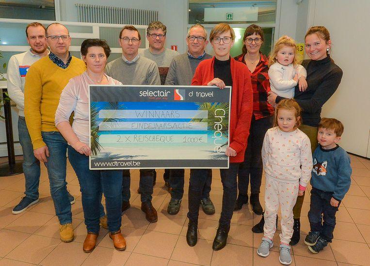De twee hoofdwinnaars, omringd door enkele bestuursleden, houden een reischeque van 1.000 euro vast. Links is dat Katleen Galloo en echtgenoot Johan Flament, rechts Lieze Persyn.
