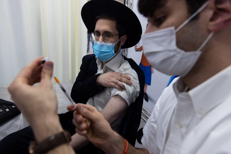Een inwoner van de Israëlische stad Bnei Brak krijgt een inenting met het Pfizer-vaccin.  Beeld Photo News