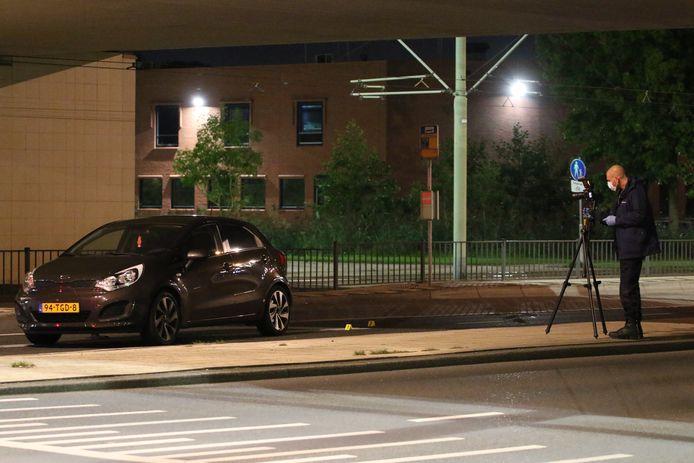 De politie doet onderzoek bij de beschoten auto.