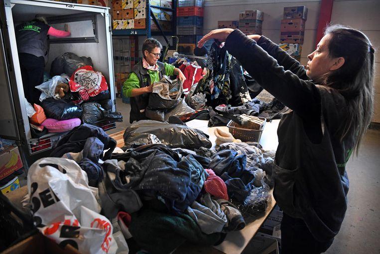 Medewerkers van een kringloopwinkel sorteren kleding. Beeld Marcel van den Bergh