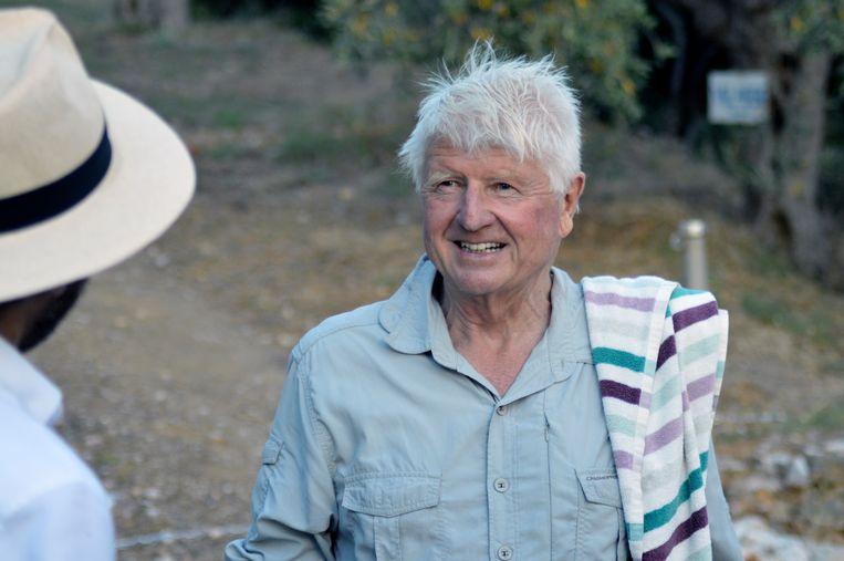 Stanley Johnson, vader van de Britse premier Boris Johnson, wordt aangesproken door Griekse verslaggevers vlakbij zijn villa 'Villa Irene' bij  Mount Pelion.  Beeld AP