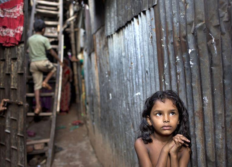 Twee kinderen in hun huis in een sloppenwijk in Bangladesh. Beeld AP