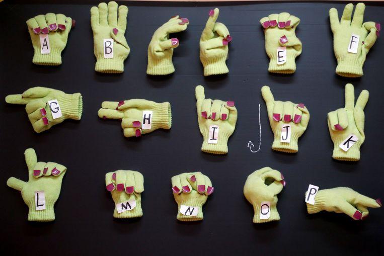 Handschoenen vormen letters uit het Engelse gebarentaalalfabet op een Palestijnse school in Nablus op de bezette Westelijke Jordaanoever. Vandaag is de Internationale Dag van de Gebarentaal. Beeld REUTERS