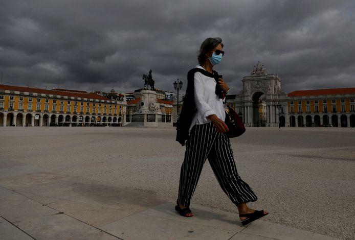 Een vrouw met mondmasker op een plein in het centrum van Lissabon.