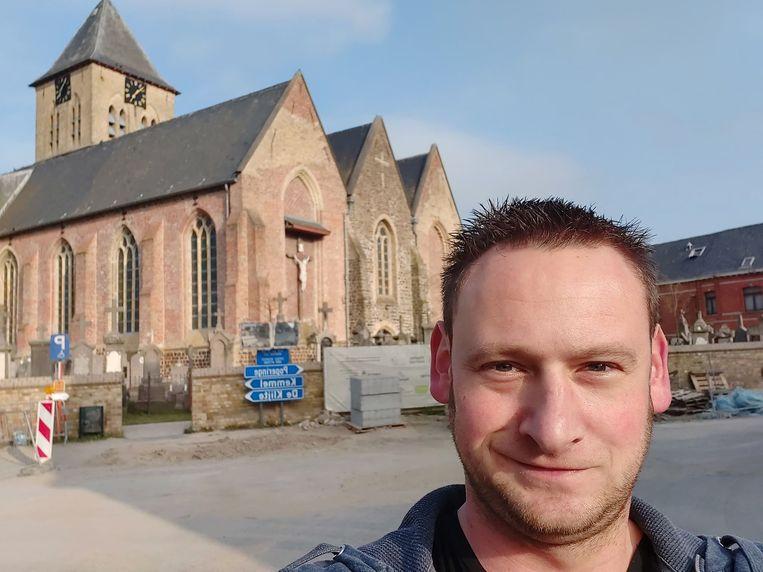 Michiel Gauquie voor de Sint-Vedastuskerk in Reningelst. Hij wil graag de klokken horen luiden in elke kerk, elke avond om 20 uur, als teken van verbondenheid en steun voor de zorgverleners.