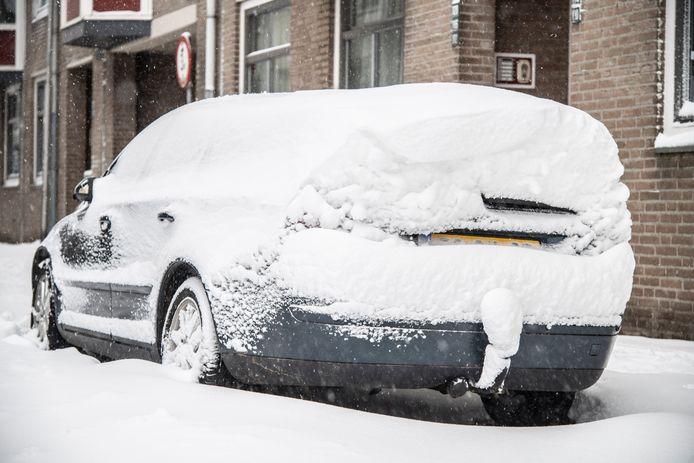 Een met sneeuw bedekte auto in Nijmegen.
