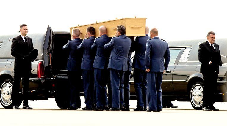 Een kist met stoffelijke resten van slachtoffers van rampvlucht MH17 wordt naar een rouwwagen gedragen in Eindhoven. Beeld ANP