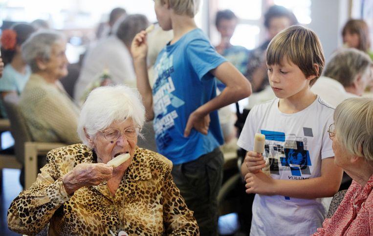 Scholieren delen in Zeist ijsjes uit aan bewoners van een verzorgingshuis. Beeld ANP