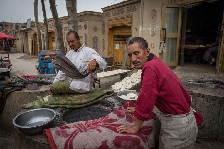 Oeigoeren bakken brood in de straten van Keriya, in de provincie Xinjiang.  Beeld LightRocket via Getty Images