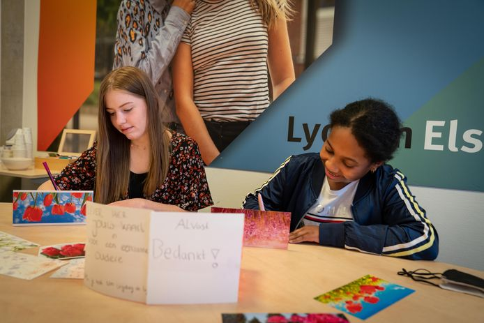 Lieve  (links) en Jada Lynn bezig met het schrijven van de kaarten aan ouderen.