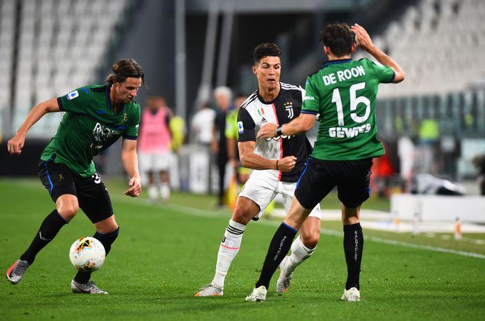 De Roon en Hateboer proberen Ronaldo de bal te ontfutselen.