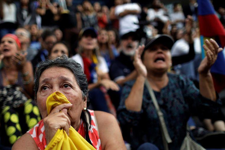 Een vrouw huilt tijdens een bijeenkomst van de oppositie in Caracas. Beeld REUTERS