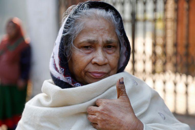 Een vrouw laat zien dat ze gestemd heeft door de inkt op haar vinger te tonen. Beeld EPA