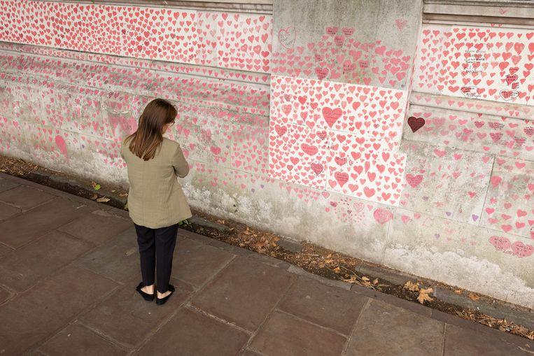 Een vrouw bestudeert de National Covid Memorial Wall in Londen.  Beeld Getty Images