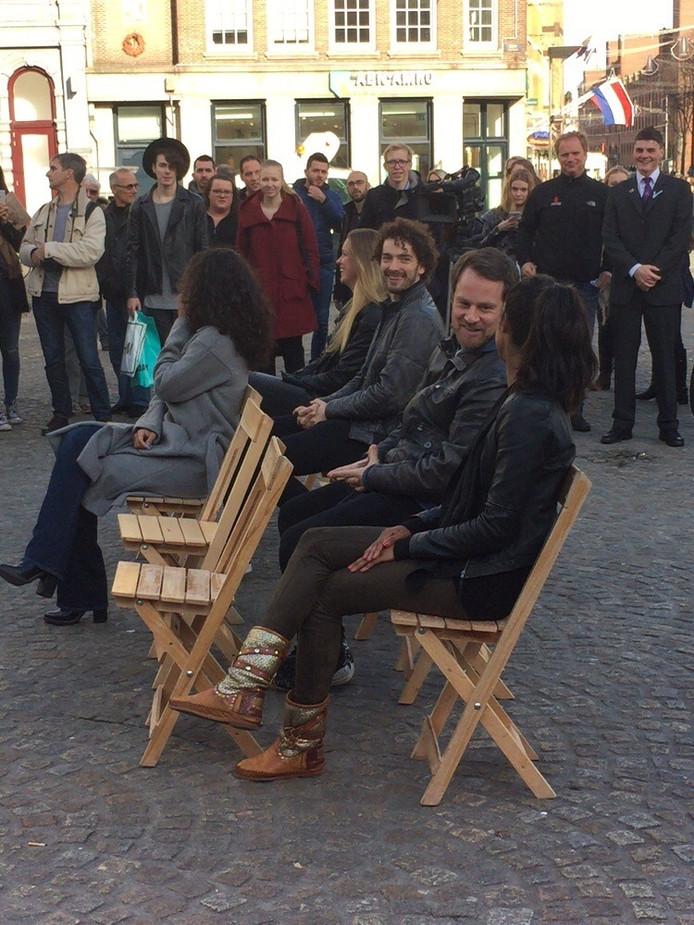 De mogelijke deelnemers op de houten stoeltjes.