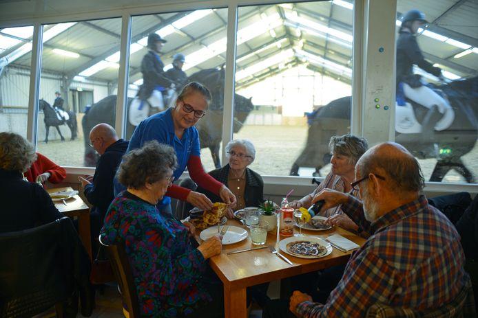 Inge Laurijs van manege Balans serveert pannenkoeken aan Geertje Nelissen, Nelly Vermaas en Corrie en Ed Dijst.