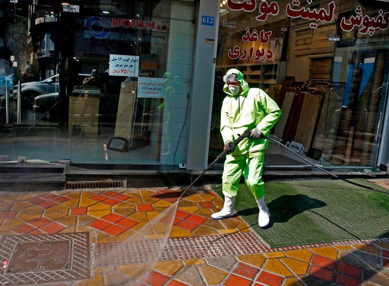 Brandweermannen en gemeentewerkers desinfecteren een straat in Teheran.  Beeld AFP