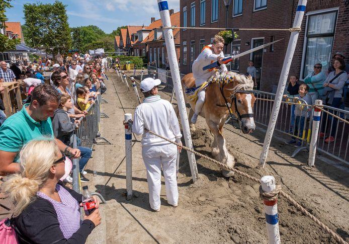 Nu de ringrijders door de Dorpsstraat van Oostkapelle galopperen, staat het publiek, in de wetenschap dat de terrassen dichtbij zijn, rijendik langs de kant.