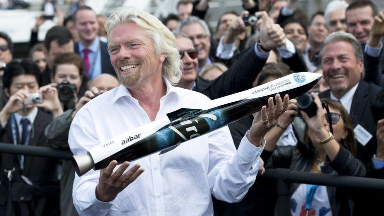 Richard Branson houdt een model vast van Launcher One voor Virgin Galactic.