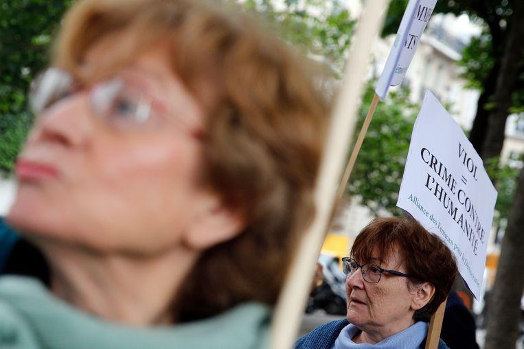 """Enkele betogers verzamelden zich gisteren voor de Assemblée Nationale in Parijs. Op één van de borden staat: """"Verkrachting = misdaad tegen de mensheid""""."""