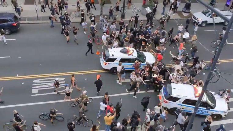Politiewagens rijden in op betogers in New York.