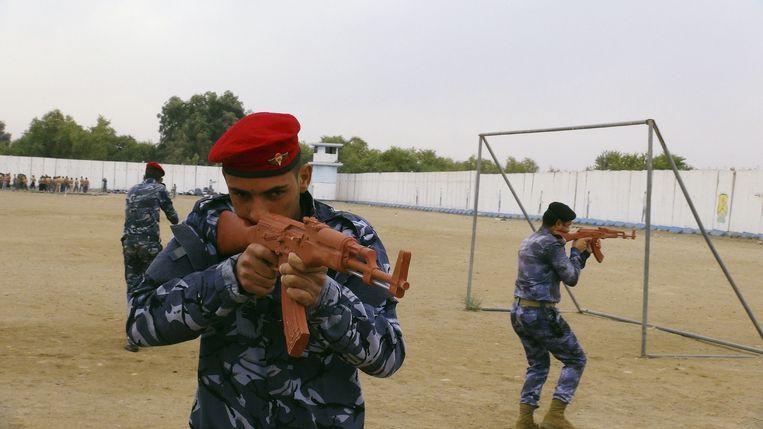 Een soennitische strijder traint met een AK-47-dummy in de woestijn, nabij Ramadi. Beeld reuters