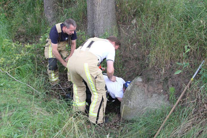 Brandweerlieden uit Enter zijn bezig een kat uit een rioolbuis te bevrijden.