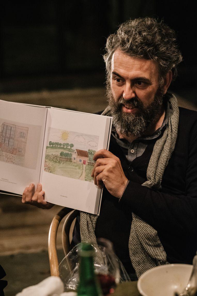 Philippe Van Cauteren toont trots zijn boek met tekeningen van vluchtelingen. Beeld Wouter Van Vooren