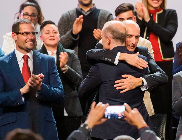 Oud-premier en partijleider Joseph Muscat wordt door Chris Fearne omhelsd. Links kijkt de nu verkozen premier Robert Abela toe. Beeld AP