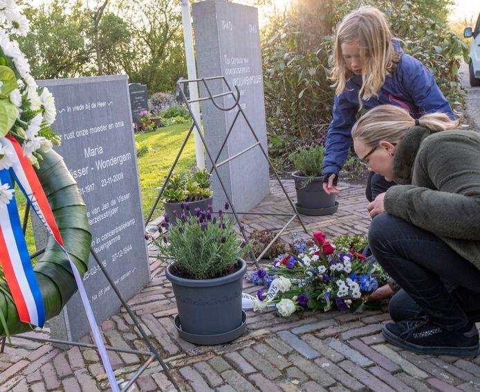 Stella (links) en Esmee leggen een krans namens de schooljeugd bij de graven van verzetsstrijder Jan de Visser (de achterste) en zijn vrouw Maria.
