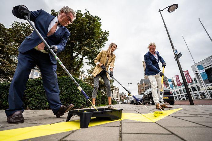 Jan Markink, Manon Flier en Jan van Dellen schilderen een bliksemflits op het trottoir tegenover het Arnhemse stadhuis.