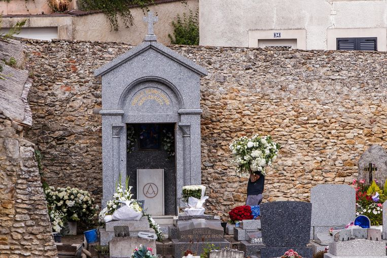 Een man draagt bloemen naar het graf van Aznavour.
