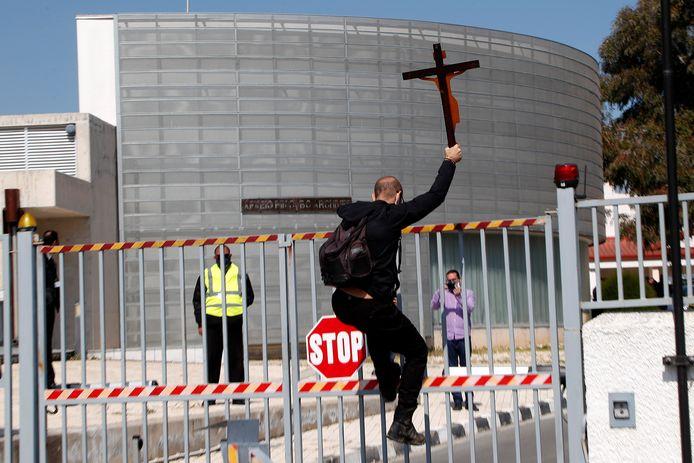 Een demonstrant probeert over het hek van de Cypische publieke omroep te klimmen.