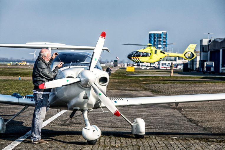 Bedrijvigheid op vliegveld Lelystad. Het oliepeil van een klein vliegtuig wordt gecontroleerd en een traumahelikopter vertrekt.  Beeld Raymond Rutting