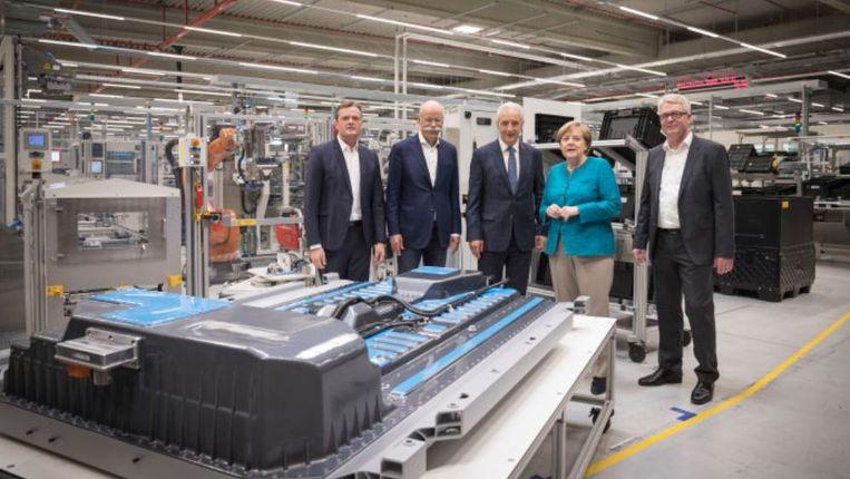 De Duitse bondskanselier Angela Merkel en Daimler-topman Dieter Zetsche (met snor) bij de bekendmaking dat een bestaande batterijfabriek voor 500 miljoen euro wordt uitgebreid. Beeld Daimler