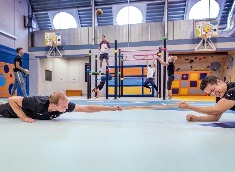 In de nieuwe gymzaal van de Academie voor Lichamelijke Opvoeding in Amsterdam draait het om de grondvormen van bewegen: rennen, vallen, klimmen, glijden, rollen en springen. Beeld Patrick Post