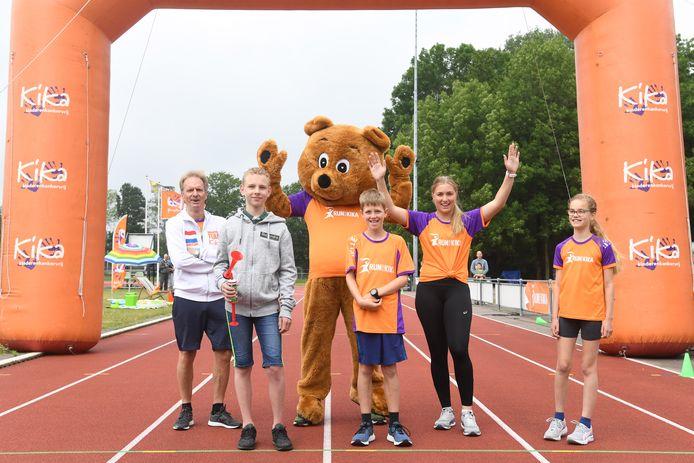 Tyro (tweede van links) geeft het officiële startsein voor de Run for Kika Summer Fun. Zijn vriend Jelle (m) doet mee aan de run.